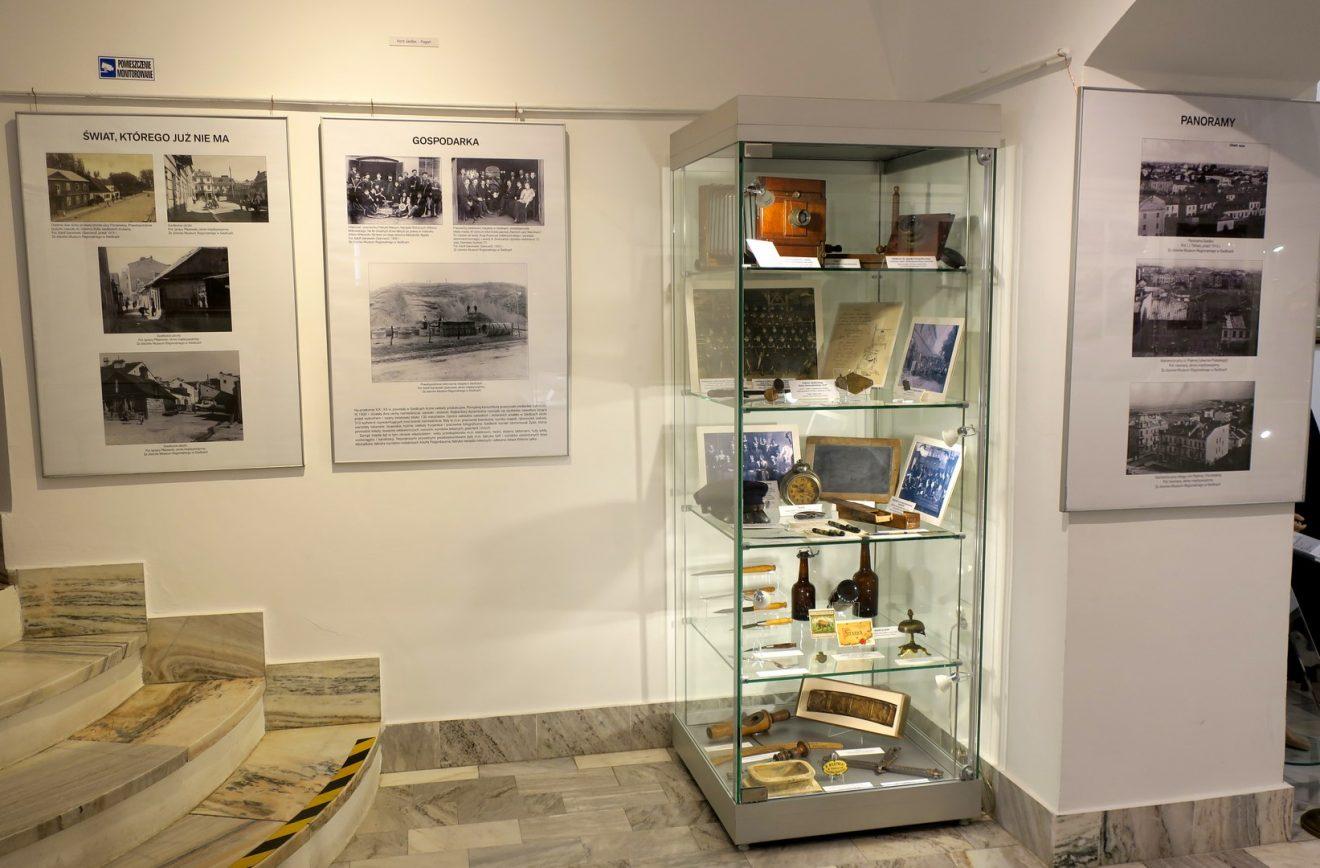 Fragment wystawy z planszami i wysoką szklaną gablotą z rzeczami codziennego użytku