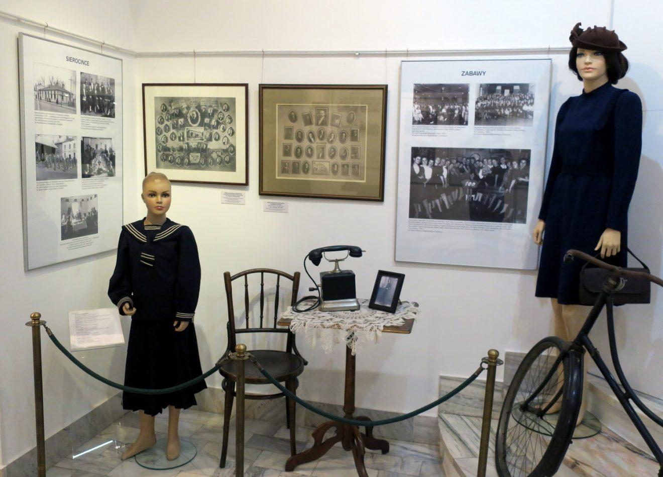Fragment wystawy z planszami i manekinami w strojach z okresu międzywojennego