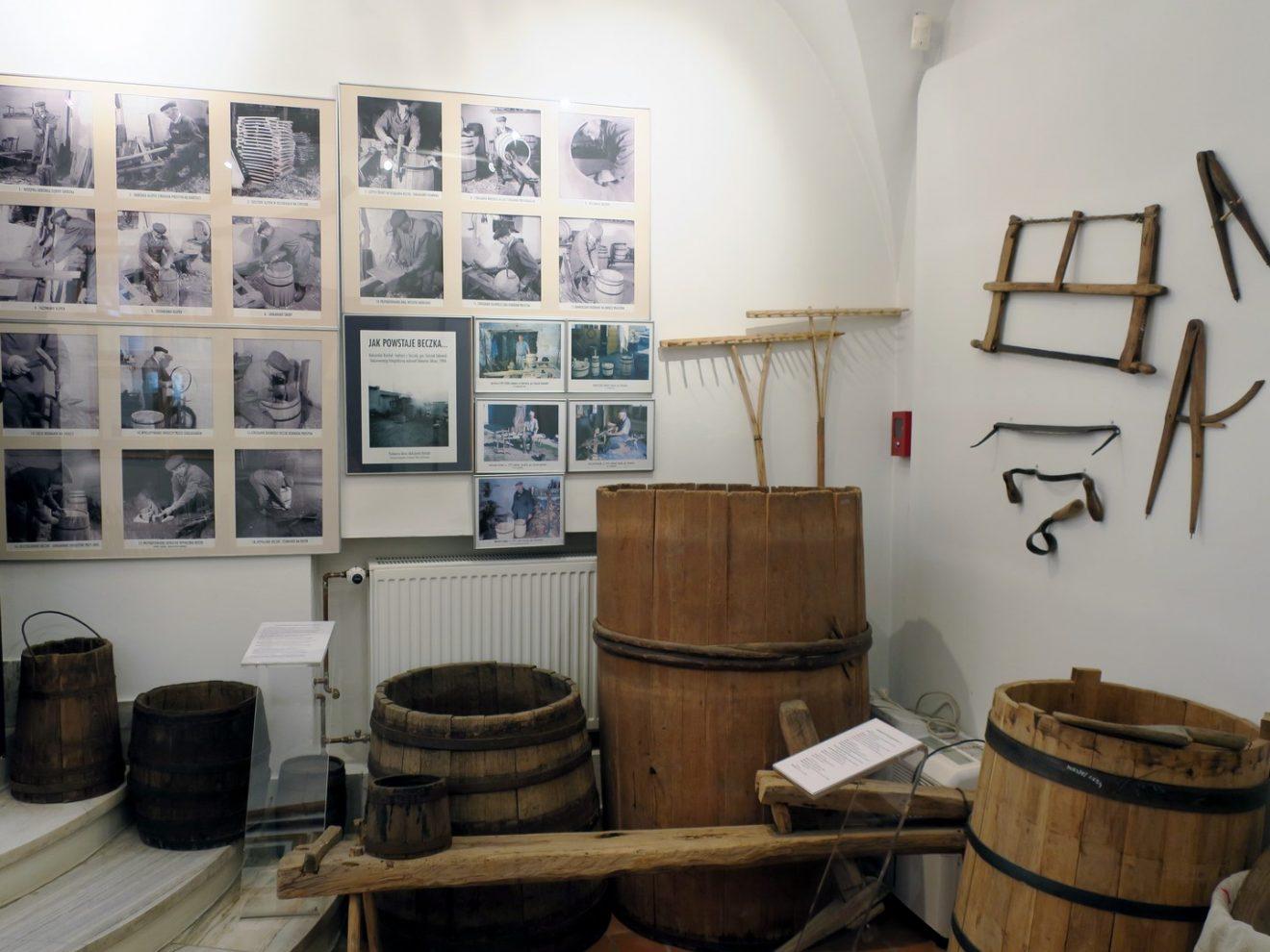 Fragment ekpozycji z drewnianymi beczkami i narzędzami do ich wyrobu