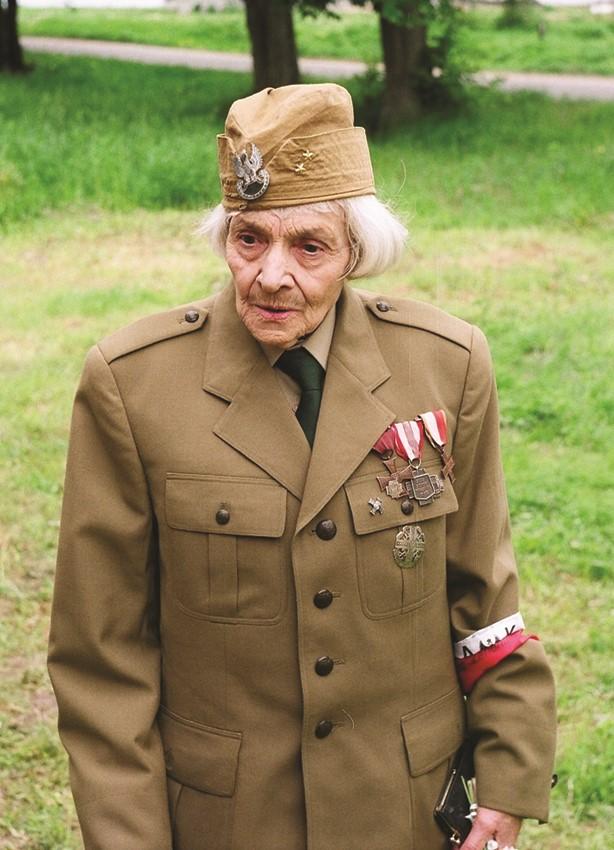 Portret kobiety w mundurze z odznaczeniami i opaską biało-=czerwoną na lewej ręce