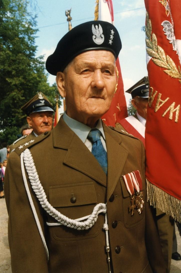 Portret starszego mężczyzny w mundurze na tle sztandaru