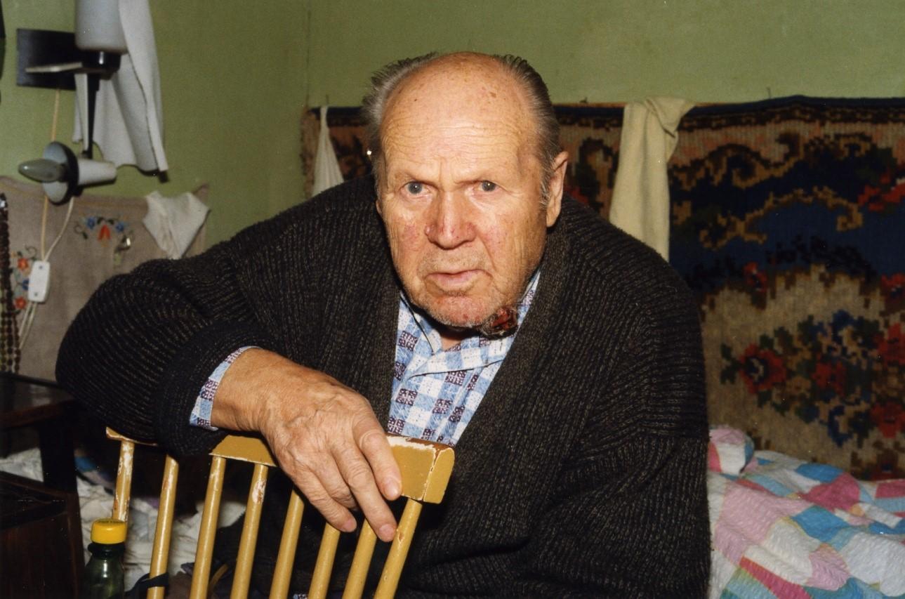 Zdjęcie siedzącego mężczyzny na łóżku opertego ręką na krześle