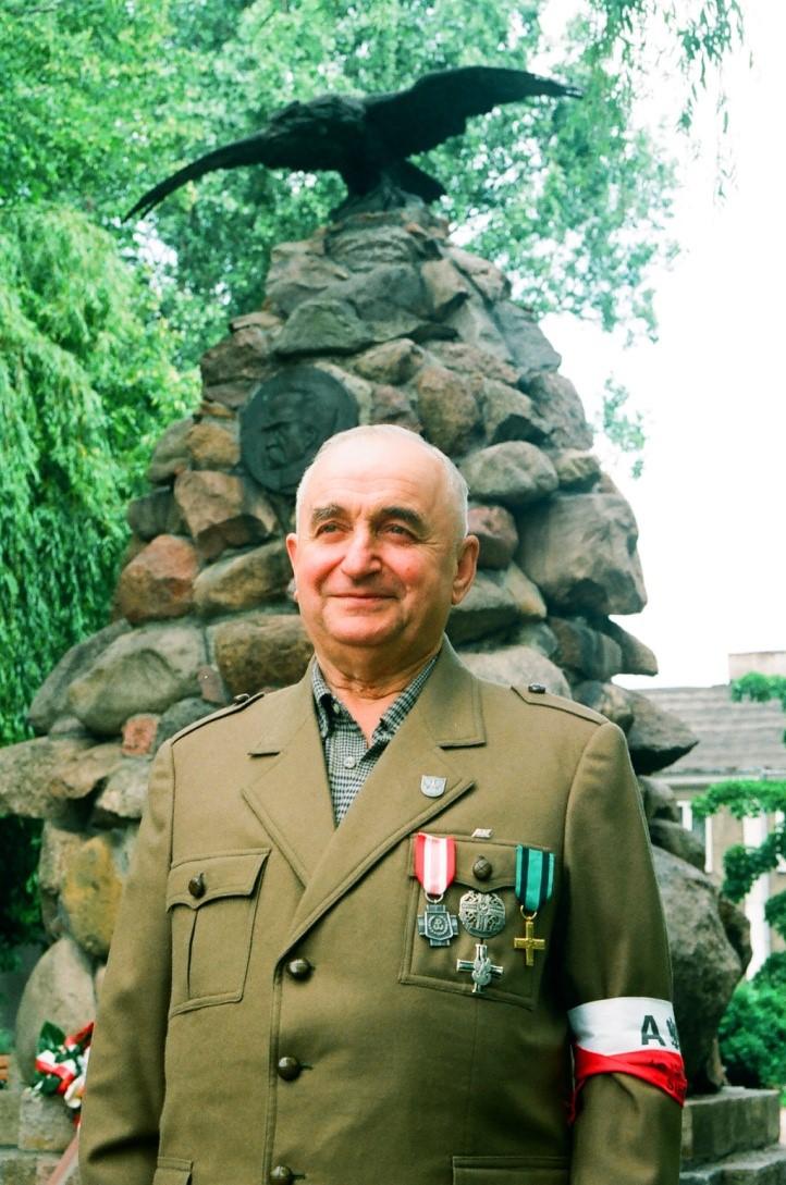 Zdjęcie mężczyzny w mundurze na tle kamiennego pomnika z orłem