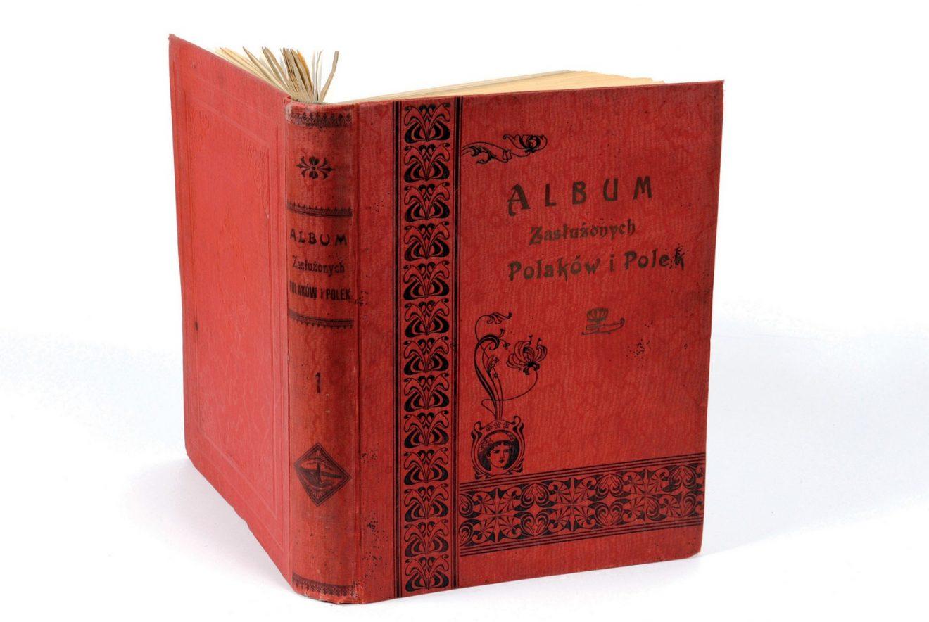 Czerwona okładka otwartej książki z roślinnymi ozdobieniami i napisami