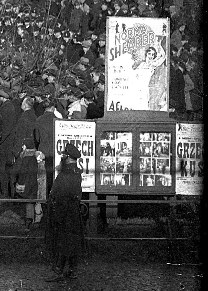afisze reklamowe w gablotach, w tle tłum ludzi