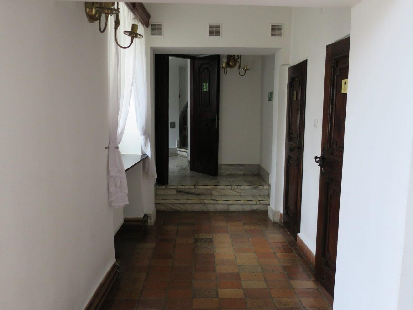 Fotografia korytarza z widocznymi schodami i zróżnicowanymi poziomami podłóg