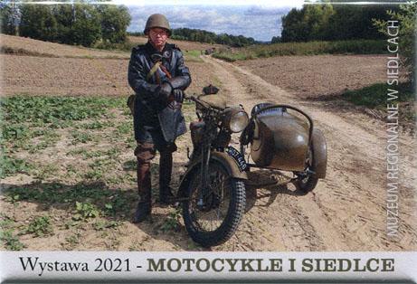 Magnes z wizerunkiem postaci mężczyzny ubranym w mundur stojącego obok motora z koszem