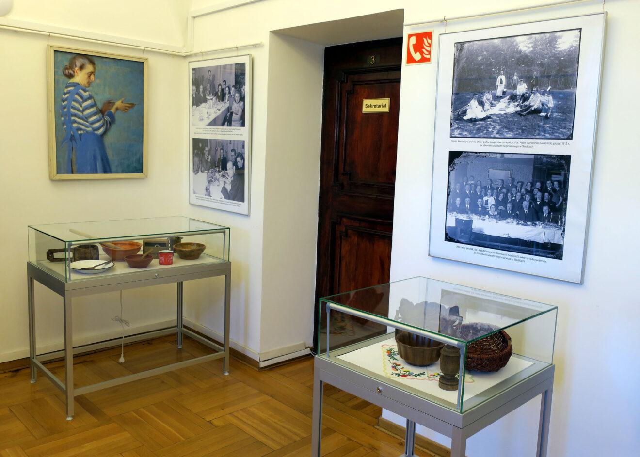 Fragment wystawy z obrazami, planszami ze zdjęciami i przedmiotami kuchennym w gablotach